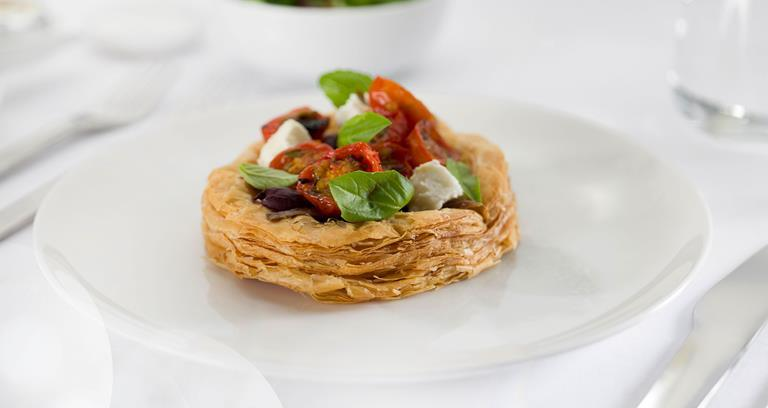 Caramelised onion tart with anchovy, roasted cherry tomatoes, goat's feta and basil